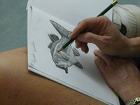 A teacher at a Salt Marsh STEAM workshop puts the finishing touches on her drawing.